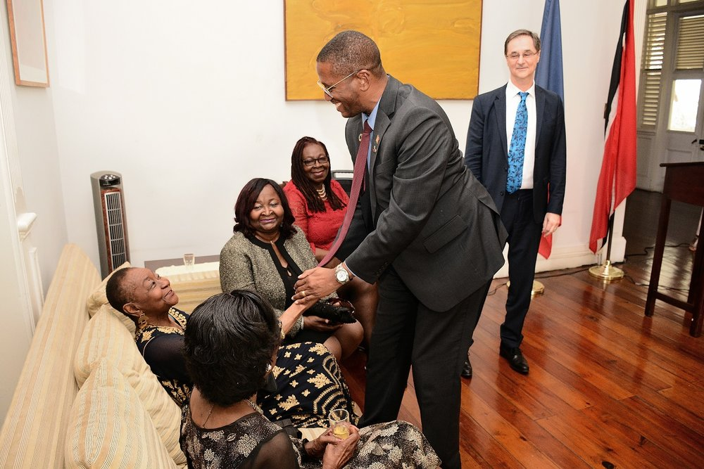 Chief Justice Ivor Archie greets Calypso Rose while her sisters and Ambassador Lavroff look on